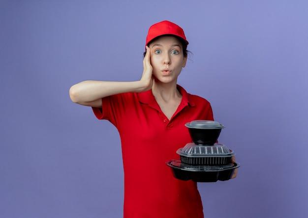 Impressionné jeune jolie livreuse portant un uniforme rouge et une casquette tenant des contenants de nourriture touchant le temple isolé sur fond violet avec espace de copie