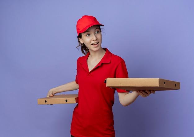 Impressionné jeune jolie livreuse portant l'uniforme rouge et une casquette tenant des paquets de pizza à côté isolé sur fond violet