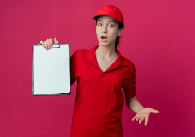 Impressionné jeune jolie livreuse en uniforme rouge et cap montrant le presse-papiers et la main vide isolé sur fond cramoisi