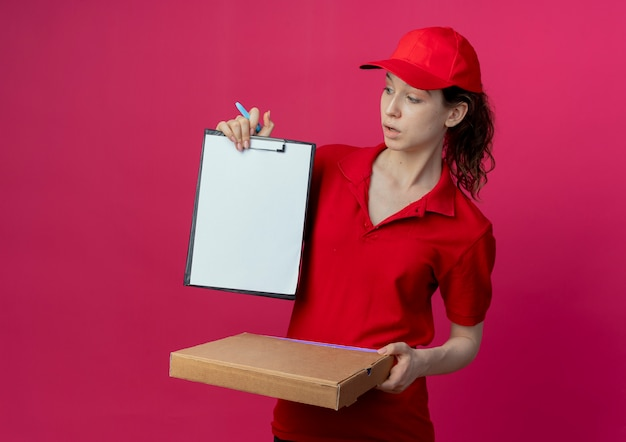 Impressionné jeune jolie livreuse en uniforme rouge et cap tenant le stylo de paquet de pizza et montrant le presse-papiers en regardant le presse-papiers isolé sur fond cramoisi avec espace de copie
