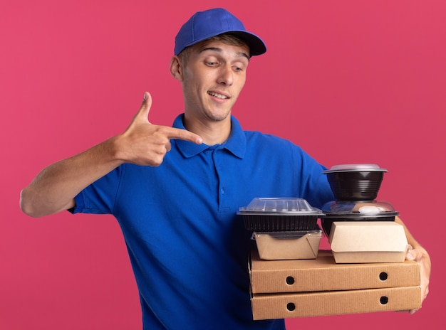 Impressionné jeune livreur blonde tient et pointe sur les contenants de nourriture et les paquets sur les boîtes de pizza sur rose