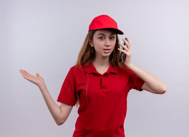 Impressionné jeune livreuse en uniforme rouge tenant un téléphone mobile et montrant la main vide sur un espace blanc isolé