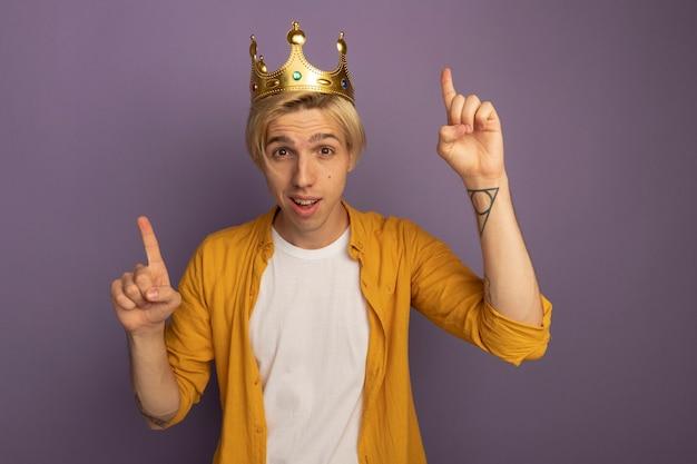 Impressionné jeune mec blond portant un t-shirt jaune et des points de couronne en haut isolé sur violet