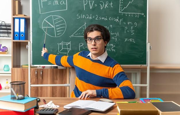 Impressionné jeune professeur de géométrie caucasien portant des lunettes assis au bureau avec des fournitures scolaires en classe gardant la main sur le bureau regardant l'avant pointant avec un bâton de pointeur au tableau