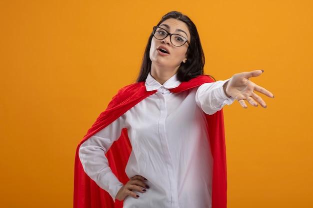 Impressionné jeune superwoman portant des lunettes à l'avant, étirant la main vers l'avant en gardant un autre sur la taille isolé sur mur orange