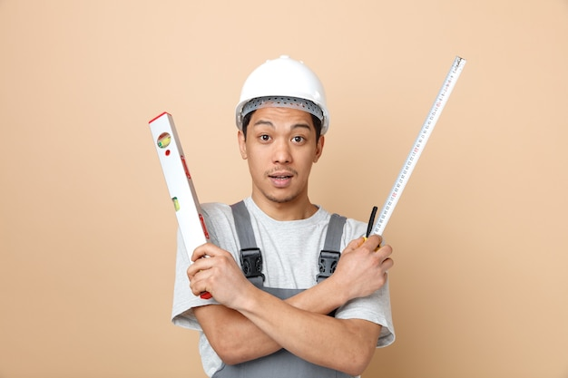 Impressionné jeune travailleur de la construction portant un casque de sécurité et uniforme tenant un mètre ruban et une règle de niveau en gardant les mains croisées