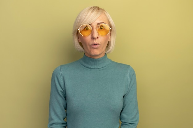 Impressionné jolie femme slave blonde à lunettes de soleil regarde la caméra sur vert olive