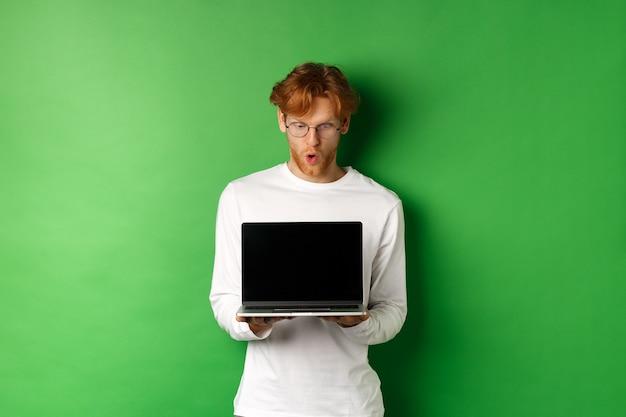 Impressionné mec ringard rousse dans des verres montrant un écran d'ordinateur portable vide et regardant l'écran étonné, debout sur fond vert.