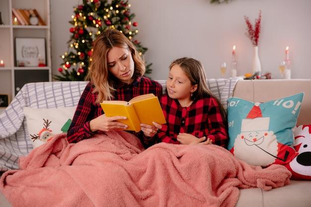 Impressionné mère et fille livre de lecture assis sur un canapé recouvert d'une couverture et profiter du temps de noël à la maison