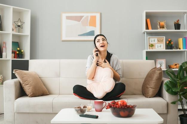 Impressionné en mettant la main sur le coeur, une jeune fille avec un oreiller parle au téléphone assise sur un canapé derrière une table basse dans le salon