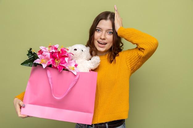 Impressionné de mettre la main sur la tête belle jeune fille tenant un sac-cadeau