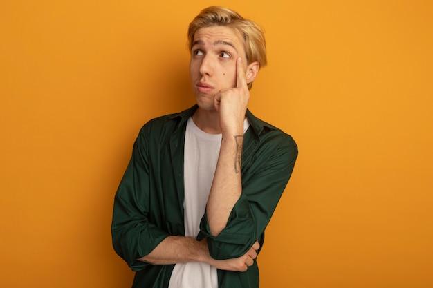 Impressionné regardant côté jeune mec blond portant un t-shirt vert mettant le doigt sur la joue