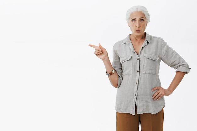 Impressionné vieille femme doigt pointé vers la gauche, posant une question sur le produit