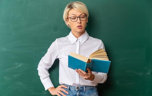 Impressionnée jeune enseignante blonde portant des lunettes en classe debout devant un tableau tenant et lisant un livre en gardant la main sur la taille