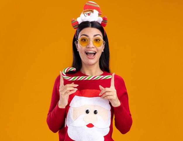 Impressionnée jeune fille caucasienne portant un bandeau de père noël et un pull avec des lunettes tenant une canne en bonbon de noël traditionnelle isolée horizontalement sur un mur orange avec un espace de copie