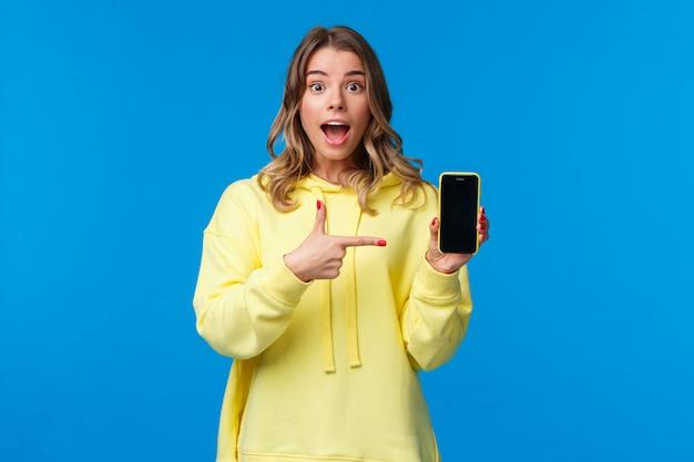 Impressionnée joyeuse fille blonde joyeuse expliquer quelque chose en pointant l'écran du téléphone portable, en parlant d'une nouvelle application ou en partageant ses photos de vacances, tenir le smartphone, regarder