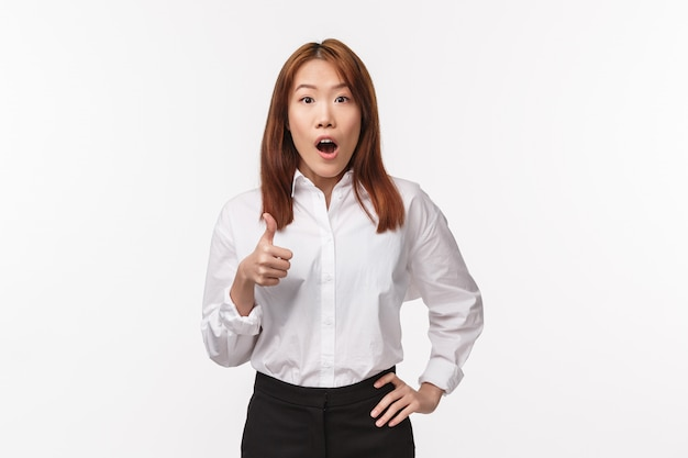 Impressionnée et sans voix, une jeune femme asiatique fascinée par un travail bien fait, montre le pouce levé, étonné de la mâchoire tombée, approuve et aime des performances incroyables