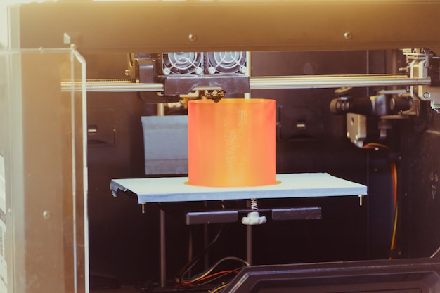 L'imprimante 3d imprime la forme d'un gros plan orange en plastique fondu. l'imprimante 3d tridimensionnelle automatique effectue une modélisation plastique en laboratoire. technologie additive moderne et progressive
