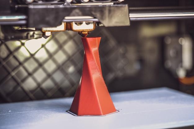 L'imprimante 3d imprime la forme d'un gros plan vert en plastique fondu. l'imprimante 3d tridimensionnelle automatique effectue une modélisation plastique en laboratoire. technologie additive moderne et progressive