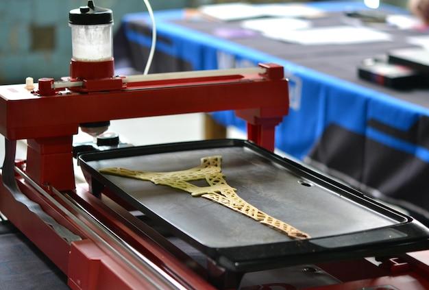Imprimante 3d qui imprime une pâte liquide. imprimante 3d imprimant des crêpes avec de la pâte liquide en gros plan de différentes formes. technologies additives modernes 4.0 révolution industrielle