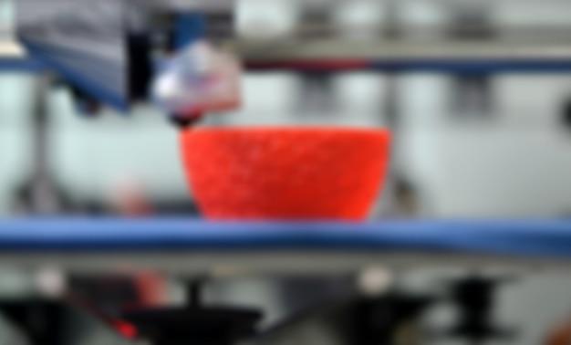 Imprimante 3d de travail à proximité. impression imprimante 3d objet plastique orange sur fond bleu. filament de fil en plastique, technologie d'impression moderne. technologie additive progressive