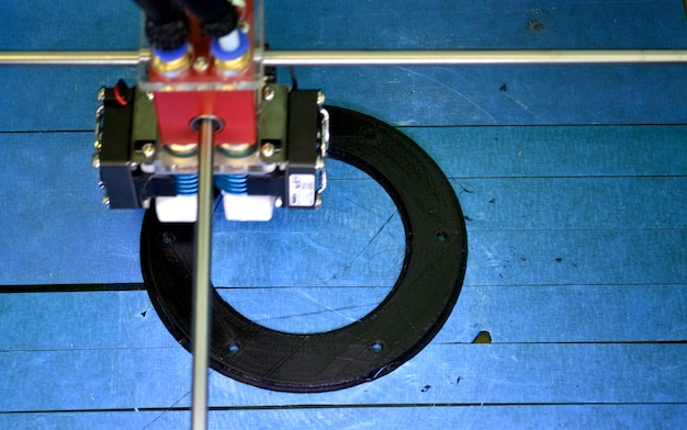 Imprimante 3d de travail à proximité. impression d'objet imprimante 3d sur fond bleu. vue de dessus. filament de fil en plastique, technologie d'impression moderne. technologie additive progressive
