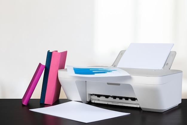 Imprimante domestique compacte sur le bureau avec des livres sur fond flou
