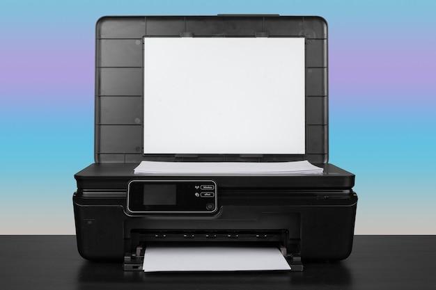 Imprimante laser compacte sur un bureau noir sur fond bleu