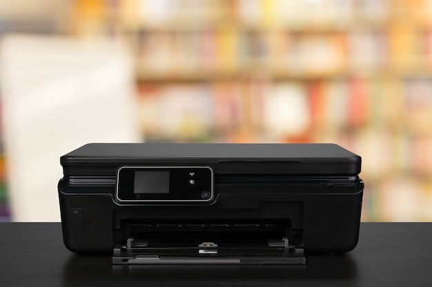 Imprimante laser compacte sur un bureau noir sur fond flou