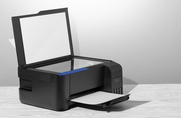 Imprimante noire avec scanner, sur table en bois blanc.