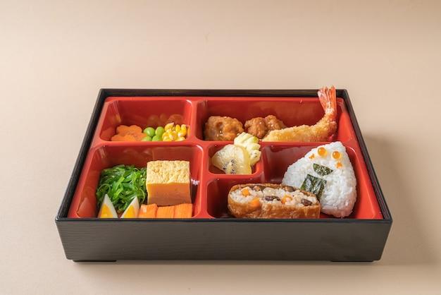 (inari sushi) riz à sushi enveloppé dans du tofu séché avec crevettes frites et poulet frit dans un ensemble bento