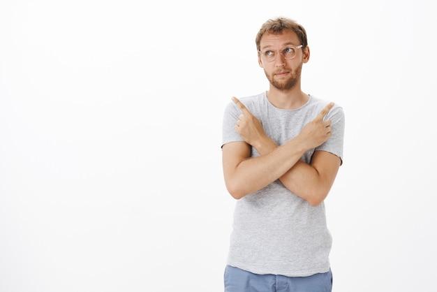 Incertain, un client masculin intelligent et créatif dans des lunettes, pinçant les lèvres et fronçant les sourcils en détournant les yeux, croisant les mains sur la poitrine pointant à gauche et à droite pour prendre une décision avec des doutes