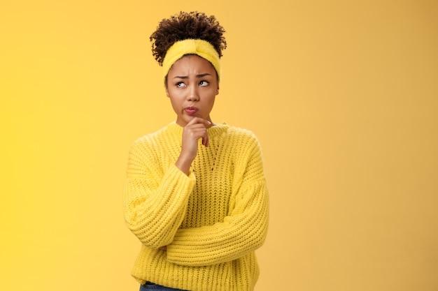 Incertain, hésitant et inquiet, une jolie fille afro-américaine fait face à une décision difficile, recherchez un plan réfléchi en pensant à la manière d'agir, touchez le menton, faites une supposition debout sur un fond jaune.