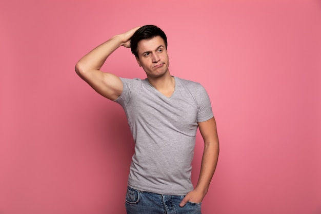 Incertain. un homme athlétique en tenue décontractée, qui touche l'arrière de la tête avec sa main droite et tient sa main gauche dans une poche.