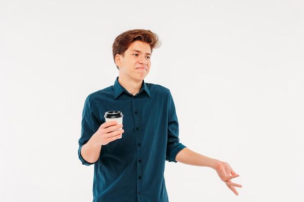 Incertain jeune étudiant doutant avec papier tasse de café sur