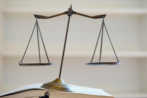 Inclinaison de l'échelle de la justice sur un livre ouvert en fond blanc symbole injistice