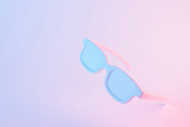 Inclinaison de lunettes blanches sur fond de couleur rose