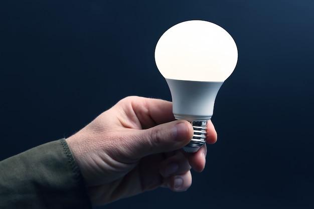 Inclus une nouvelle lampe à led dans la main humaine sur fond sombre