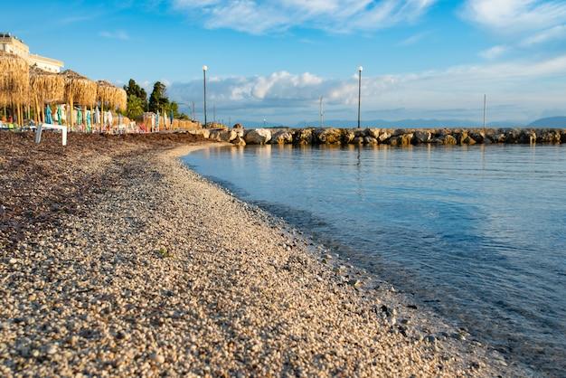 Incroyable baie aux eaux cristallines sur l'île de corfou, grèce. beau paysage de plage de la mer ionienne. temps ensoleillé, ciel bleu.