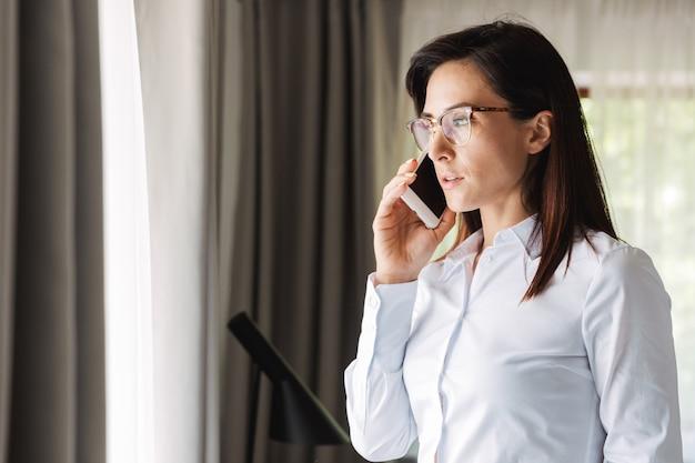 Incroyable belle jeune femme d'affaires dans des vêtements de cérémonie à l'intérieur à la maison parlant par téléphone portable.