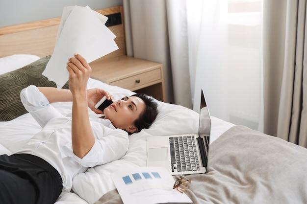 Incroyable belle jeune femme d'affaires dans des vêtements de cérémonie à l'intérieur à la maison se trouve sur le lit en train de parler par téléphone tenant des documents papier.