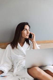 Incroyable belle jeune femme d'affaires à l'intérieur à la maison à l'aide d'un ordinateur portable parlant par téléphone mobile.