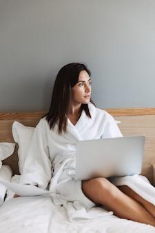Incroyable belle jeune femme d'affaires à l'intérieur à la maison à l'aide d'un ordinateur portable.