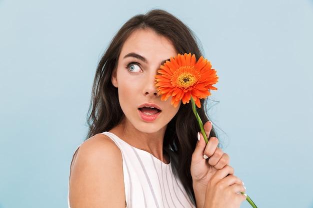 Incroyable belle jeune femme isolée mur tenant une fleur.