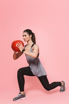 Incroyable belle jeune femme jolie fitness faire des exercices de sport avec ballon isolé sur mur rose