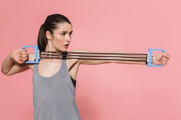 Incroyable belle jeune jolie femme de remise en forme faire des exercices de sport avec un équipement isolé sur un mur rose