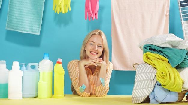 Incroyable blonde assise à une table et sur un mur bleu isolé, concept de femme au foyer