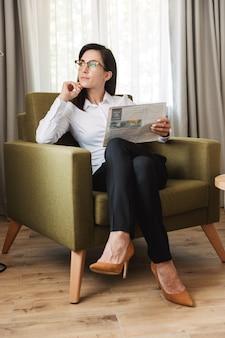 Incroyable concentré belle jeune femme d'affaires dans des vêtements de cérémonie à l'intérieur à la maison en lisant le journal.
