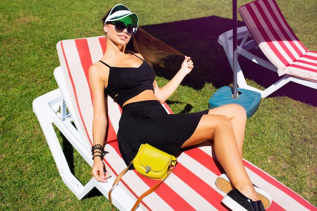 Incroyable concept sportif de mode de rue, portrait d'une jolie fille. portez un chapeau néon et un look noir d'hôtel, des lunettes de soleil noires. femme d'automne. style bohème artsy. mode automne.