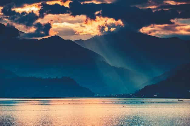 L'incroyable coucher de soleil de conte de fées sur le lac phewa d'eau douce. le ciel nuageux coloré à couper le souffle. la principale attraction touristique de la ville de pokhara au népal.